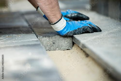 Builder laying new paving bricks - 183128031