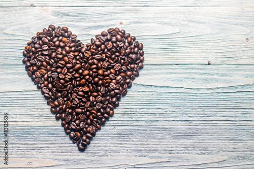 Staande foto Koffiebonen Кофейные зерна выложены в форме сердца с корицей и бадьяном на деревянном фоне бирюзового цвета