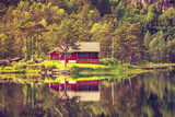 wooden cabin in forest on lake shore, Norway - 183134216