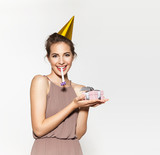 Happy smiling lady with festive hat and whistle looking at camera. Portrait of funny girl with confetti isolated on white background. Concept of the holiday or birthday party.