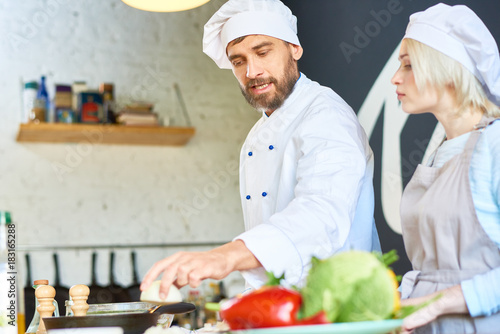 Sticker Handsome bearded chef wearing uniform explaining pretty woman how to prepare vegetable soup correctly while conducting cooking workshop at modern restaurant kitchen