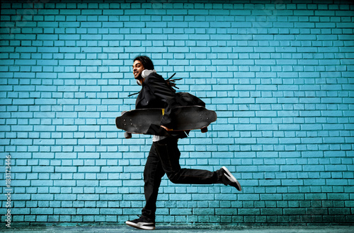 Fotobehang Skateboard Smiling hipster dreadlock skater with headphones running in a suit near the blue wall on the street.
