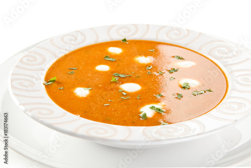 Tomato soup with cream on white background  - 183174663