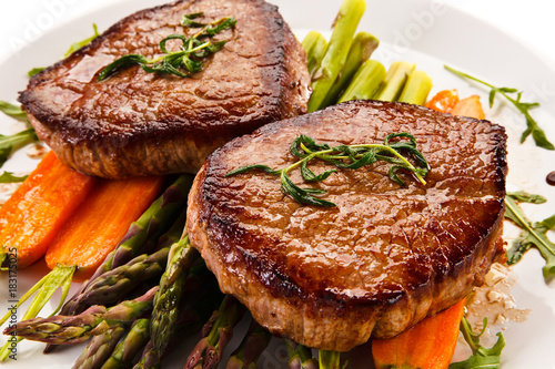 Plexiglas Steakhouse Grilled beef steaks with asparagus and carrots on white background
