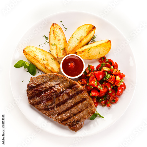 Foto op Canvas Steakhouse Grilled steak, baked potatoes and vegetable salad on white background
