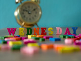Colorful wooden word WEDNESDAY on wooden table and vintage alarm clock and background is powder blue. English alphabet made of wooden letter color. - 183179843