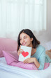 Asian girl in bed at home, happy holding greeting card with red heart shape.