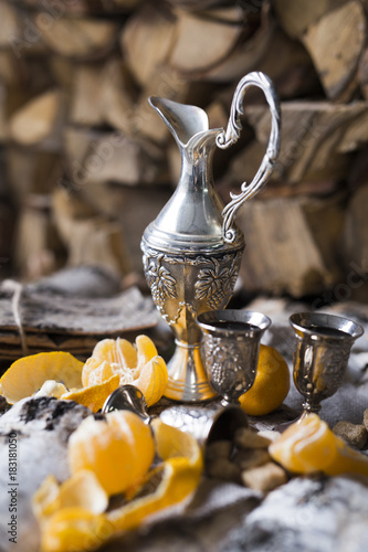 Poster silver decanter of brandy, glasses of brandy in rustic style on wooden surface in the snow
