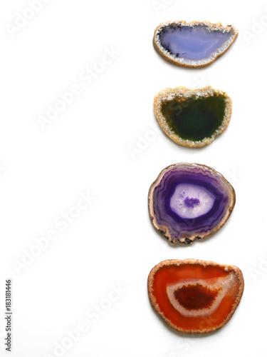Skład kamieni naturalnych z kawałkami agatu. Niebieskie, zielone, fioletowe i pomarańczowe kamienie. Naturalny agata zbliżenie odizolowywający na białym tle.