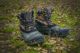 A pair of worn hiking boots on natural background. Dirty boots for hiking, fishing, traveling. - 183196616