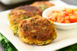 Zucchini, couscous and parsley fritters with tomato and onion dip on the side, photographed with natural light (Selective Focus, Focus in the middle of the first fritter) - 183196867