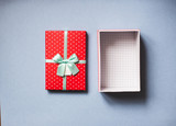 Open red gift with bow on blue background top view.