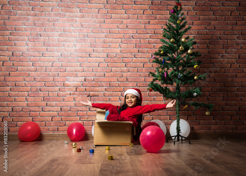 Cute little indian girl in red sweater and santa hat sitting inside empty Cardbo Poster