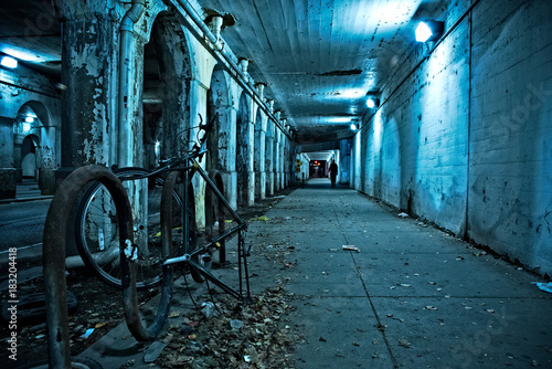 Foto op Canvas Groen blauw Gritty dark Chicago city street under industrial train bridge viaduct tunnel with bicycle and person at night.