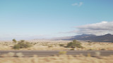 Driving plate side view moving through desert in car with motion blur - 183205893
