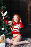 girl in sexy lingerie and red sweater making selfie image on christnas tree background