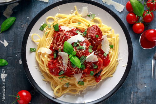 Spaghetti pasta meatballs with tomato sauce, basil, herbs parmesan cheese on dark background - 183209027