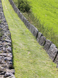 mountain path bordered by stone blocks - 183211805