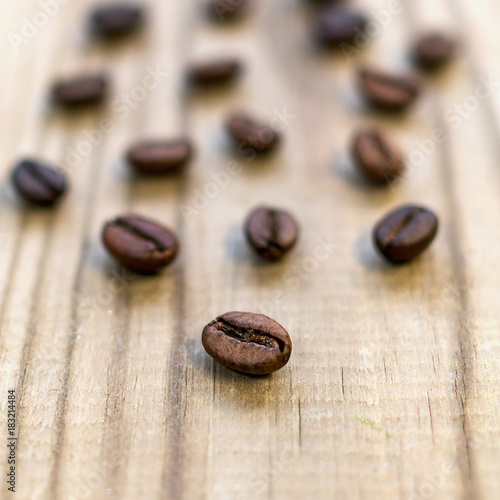 Poster Koffiebonen Grains of coffee scattered on a wooden table.
