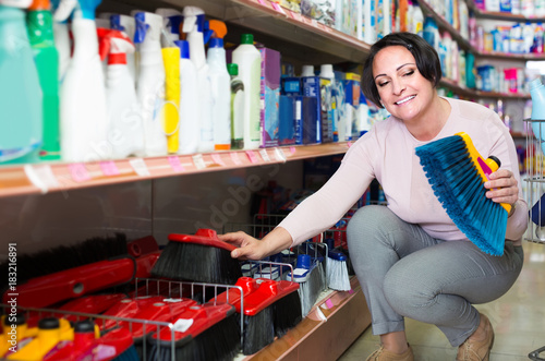 mature woman choosing cleaning brush in household department