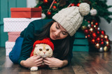 Portrait of young woman and cute cat wearing sweater and knitted hats. christmas tree and presents background - 183218250