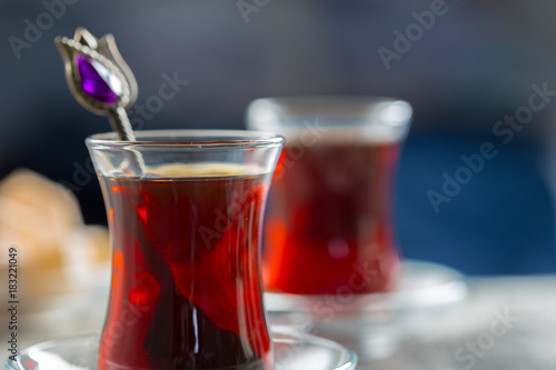 Wall mural Red tea in turkish glasses on a wooden table