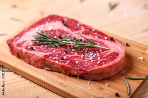 Foto op Canvas Steakhouse raw uncooked marble beef steak ribeye with rosemary on wooden desk, ready to fry