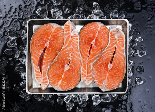 Foto op Canvas Steakhouse Salmon steaks on ice on black background