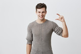 Handsome man wearing sweater showing something little with hands while gesturing and broadly smiling. Dark-haired caucasian male model demonstrating size of something against gray studio wall