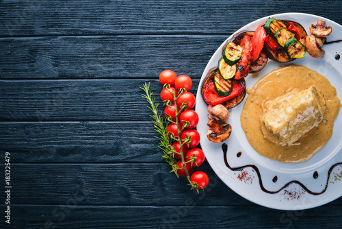 Foto op Canvas Steakhouse Meat steak with sauce and grilled vegetables. Steak Voronov. On a wooden background. Free space for your text. Top view.