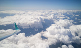 Panoramic view to the cloudscape from airplane window. The wing on the left, fluffy clouds and blue sky.  - 183229496