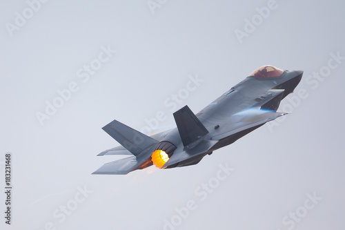 obraz PCV F-35 Lightning II in a high-G maneuver, with afterburner on and condensation trails at the wing's edge