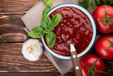 Tomato ketchup sauce in a wood  bowl with  herbs and  tomatoes on rustic background, flat lay. - 183234812