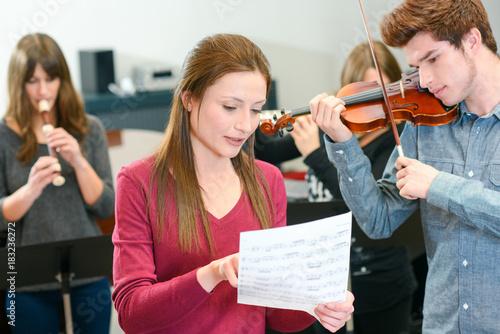 Fototapeta music teacher tutoring young man to play violin
