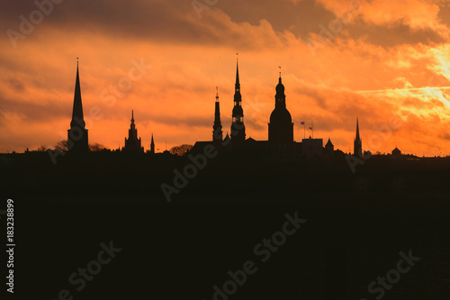 Poster London City silhouette of Riga, Latvia in colorful morning sunset. Church towers and popular landmarks in background with stunning yellow sky.