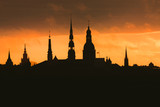 City silhouette of Riga, Latvia in colorful morning sunset. Church towers and popular landmarks in background with stunning yellow sky.