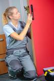 Woman fitting lock mechanism to door - 183239698