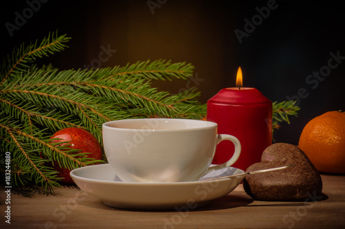 Papiers peints The cup of tea, burning candle and Christmas tree branch in the evening