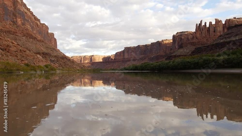 Red rocks float past as the sunrise shines on the Green River.