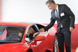 client and seller talking about lamborghini at luxury car dealer