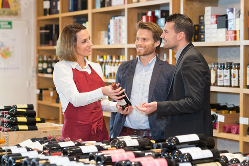Fototapeta female wine merchandiser and her customers