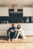 Couple sitting on kitchen floor and having coffee - 183249830