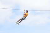man going down a zip line - 183253423