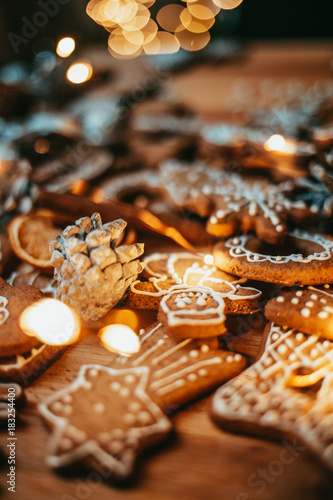 Freshly baked and homemade gingerbread cookies and food decorations on wooden table, flat lay view from above. Christmas handmade bakery. Family festive culinary and New Year traditions concept.