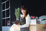 Portrait of a smiling Asian entrepreneur standing behind her cafe counter writing something on notebook. - 183263677