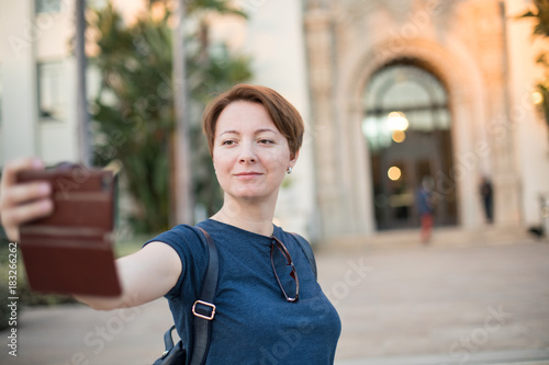 Confident young woman taking selfie in front of a beautiful historical building