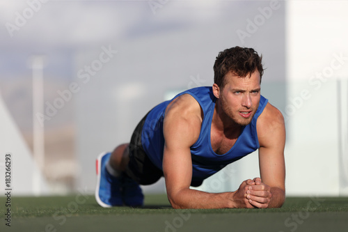 Crossfit training fitness man doing plank core exercise working out his midsection core muscles. Fit male fitness instructor planking exercising outside in summer park grass. Outdoor stadium.