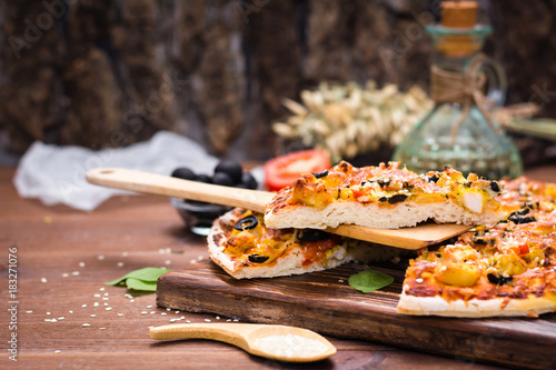 Sliced pizza with chicken, tomatoes, cheese and black olives Poster