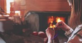 Young Woman Knitting by the Fireplace. SLOW MOTION 4K. Girl relaxes by warm fire making handmade gifts for her family. Cozy atmosphere. Winter and Christmas holidays concept. - 183281235