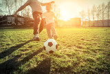 Father and son playing together with ball in football under sun - 183282621